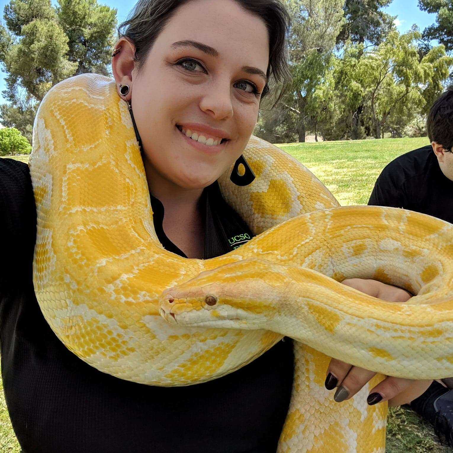 photo of myself with a large albino Burmese python draped around my shoulders and arm