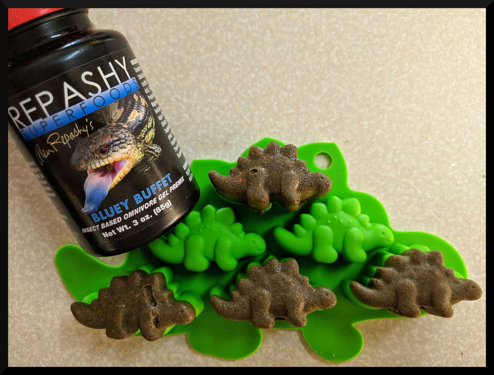 repashy gel food bottle next to green silicone mold in shape of dinosaurs